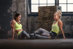 Two girls sitting down after workout