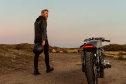 Café Racer Honda with man holding mc-helmet in sunset