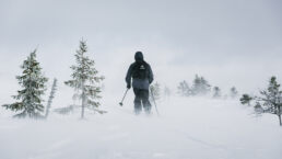 Snowboarder with Jones Snowboard backpack hiking in storm